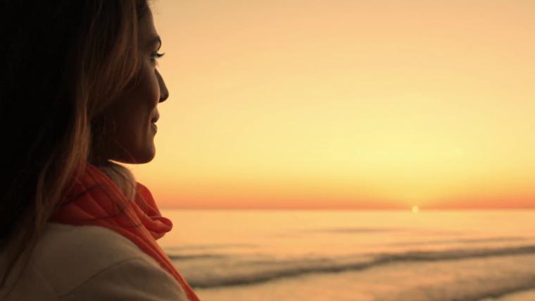 woman-looking-at-ocean-in-sunset_mkfdfbi9__F0000